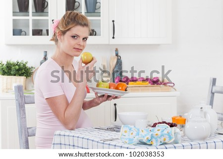 Beautiful pregnant woman with fresh fruit on the  house kitchen.