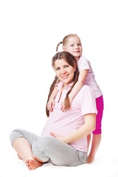 Beautiful pregnant woman with her daughter. Isolated on white background