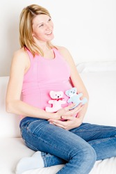 Beautiful pregnant woman with two soft toys on white sofa