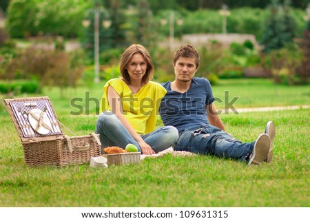 beautiful pregnant woman with young happy man having picnic