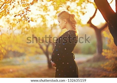 beautiful pregnant young woman outside, warm sunny picture