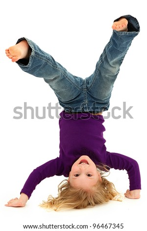 Beautiful Preschool Girl Child Laughing and Doing Hand Stand Over White Background
