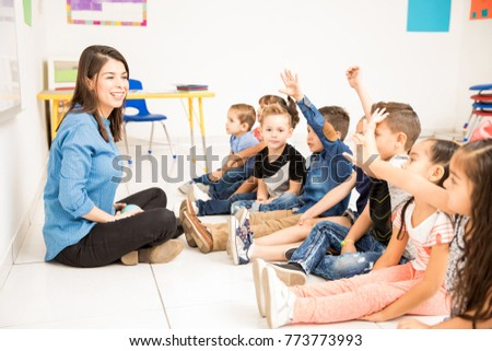 Beautiful preschool teacher and her group of students raising their hands and having some fun at school