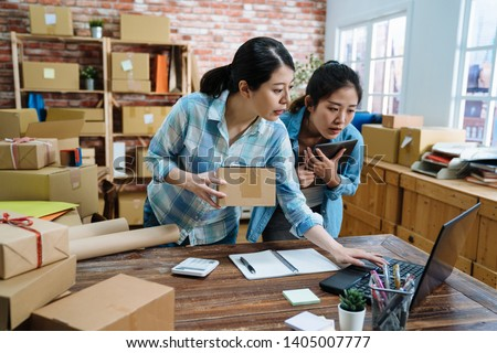 beautiful pretty female employees using laptop computer working in warehouse and browsing online shopping order document to confirm stock goods. young girls holding parcel cardboard checking notebook #1405007777