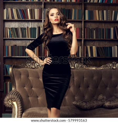 Beautiful pretty girl in black sheath cocktail dress posing in luxury library interior. Young female model fashion portrait #579993163
