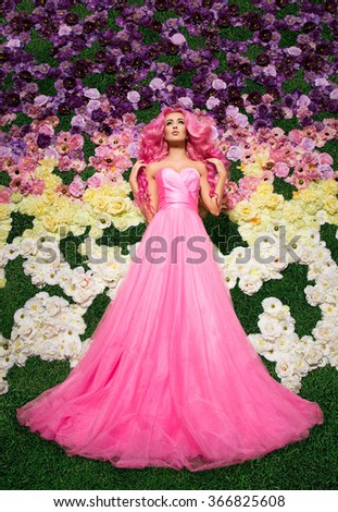 Beautiful, pretty, happy rose long and curly hair woman in wedding dress posing. Model like a doll, barbie, in interior studio shooting, with colorfull roses, flowers. Green grass, glade.