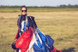 Beautiful pretty woman skydiver holding a parachute canopy after landing.