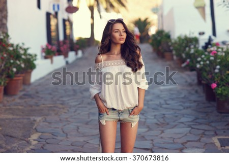 Beautiful pretty woman walking at old town pavement street and looking away. Travel concept