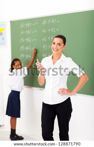 beautiful primary maths teacher in front of chalkboard in classroom