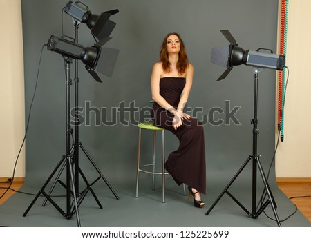 beautiful professional female model resting between shots in photography studio shoot set-up - Shutterstock ID 125225699