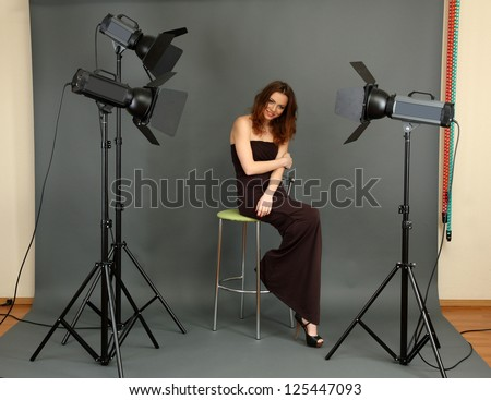 beautiful professional female model resting between shots in photography studio shoot set-up - Shutterstock ID 125447093