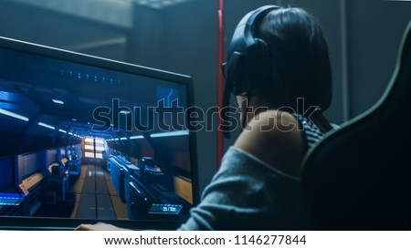 Beautiful Professional Gamer Girl Playing in First-Person Shooter Online Video Game on Her Personal Computer. Casual Cute Geek Girl Wearing Headset. In the Underground Gaming Club. #1146277844