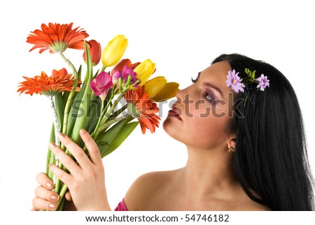 Beautiful profile of a young woman holding up in her hands a bouquet of spring flower and admire or smell them