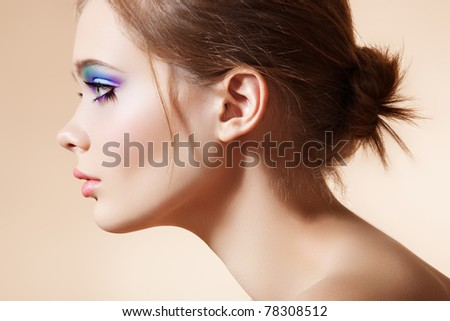 Beautiful profile view of female model face with bright fashion make-up and simple sensuality hairstyle on beige background