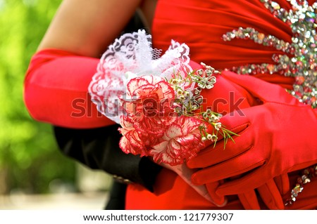 Beautiful prom couple showing off the her elegant gloves and corsage.