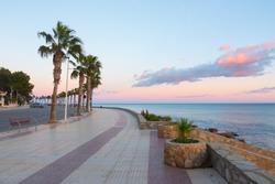 Beautiful promenade (boardwalk) near the mediterranean shore. Amazing sunset colors in the sky. Paseo Maritimo Alcossebre, Castellon province, Valencian Community, Spain.