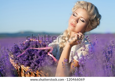 Beautiful provence woman relaxing in lavender field watching on sunset holding basket with lavanda flowers. Series. alluring girl with purple lavender. blond lady in blossom field . Ukraine - Crimea