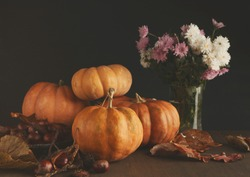 Beautiful pumpkins with leaves, chestnuts and flowers on black background with copy space for text. Cozy autumn mood, fall, holiday, halloween or thanksgiving concept