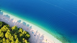 Beautiful Punta Rata beach in Brela, Croatia, aerial view. Adriatic Sea with amazing turquoise clean water and white sand on the beach.