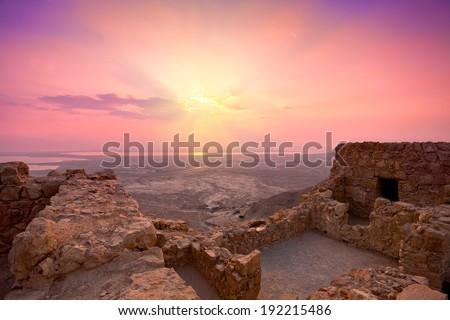 Beautiful purple sunrise over Masada fortress. Ruins of King Herod's palace in Judaean Desert.