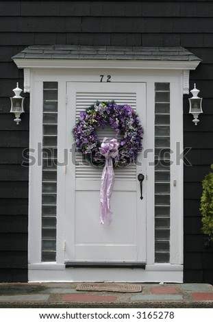 beautiful purple wreath on white door - stock photo