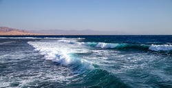 Beautiful raging seas with sea foam and waves. Background of turquoise waves.