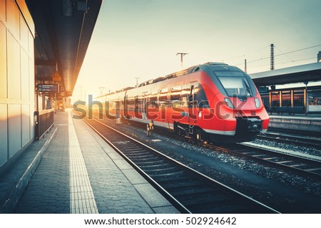 Beautiful railway station with modern high speed red commuter train at colorful sunset. Railroad with vintage toning. Train at railway platform. Industrial concept. Railway tourism #502924642
