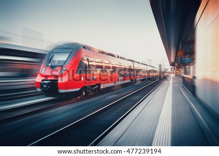 Beautiful railway station with modern high speed red commuter train with motion blur effect at sunset. Railroad. Vintage toning. Railroad travel background, tourism. Industrial #477239194