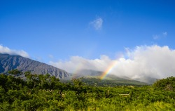 Beautiful rainbow as seen from East Maui's south coast on Piilani Highway. The mountains belong to Haleakala crater, which summits at 10,027 ft. Beautiful sunny day with some clouds - Maui, Hawaii.