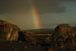 beautiful rainbow on a background of stones on a northern Norwegian evening after rain