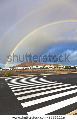 beautiful rainbow over the mountain with dark clouds