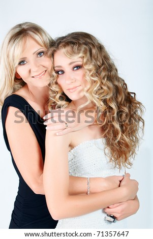 beautiful real couple mother in her 40s and teenage daughter wearing evening wear and make-up in studio