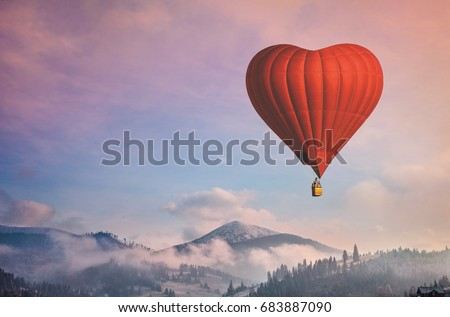 Beautiful red air balloon heart shape against blue and pink pastel sky in a sunny bright morning. Foggy mountains in the background. Romantic trip on Valentine's Day. Sport and recreation travel theme #683887090