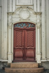 Beautiful red and detailed crafted dual door with white pillars  and vaulted top