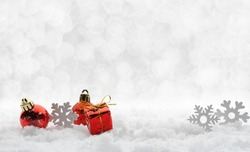 Beautiful red and white Christmas decoration toys snowflakes and balls, gift box with snow in the background and light silver bokeh with copy space. New year, Merry Christmas greiting card.
