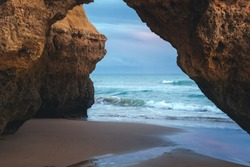 Beautiful red arch framing the ocean and the horizon on Algarve Beach, Portugal