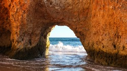 Beautiful red arch framing the ocean and the horizon on Alvor Beach, Praia dos Tres Irmaos, Algarve, Portugal