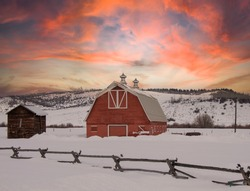 Beautiful red barn in rural Wyoming surrounded by snow as a gorgeous sunset colors the landscape hints or orange, red, and purple during winter, no people