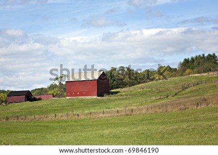 Beautiful Red barn, pasture with fence  and blue sky
