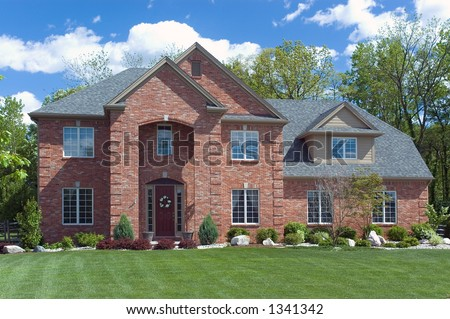 Beautiful red brick  home. Very colorful photo with blue sky and green grass. Typical new home in the suburbs of the United States. Just one of many home or house photos in my gallery.