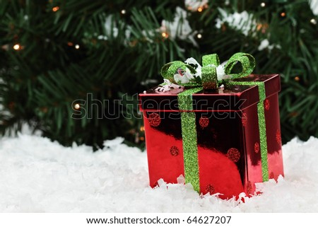 Beautiful red Christmas gift lies in the snow with a Christmas tree background. Shallow DOF.