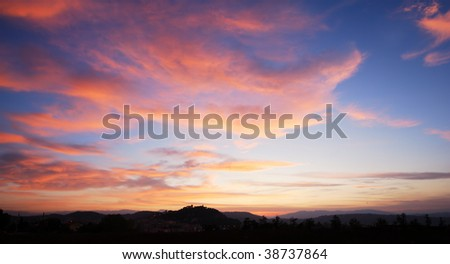 Beautiful red clouds in blue sky with silhouette of Campobasso castle
