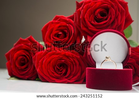 Beautiful red flowers rose. Gold jewelry at box.