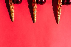 Beautiful red gradient Christmas background and lots of empty space for text. Christmas tree toys in the shape of orange icicles and red round shiny balls on top.