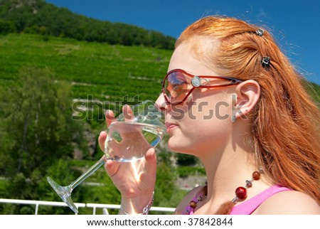 Beautiful red hair woman drinking a glass of water