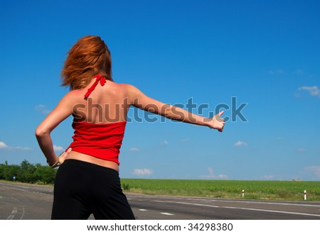 Beautiful red hair woman hitch hiking
