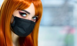 Beautiful red-haired girl in a black medical mask with bright professional makeup. Beauty during quarantine and isolation.