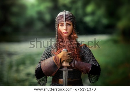 Beautiful red haired girl in metal medieval armor dress with sword standing in warlike pose and looking at camera with fearless. Fairy tale story about warrior . Warm art work. - Shutterstock ID 676191373
