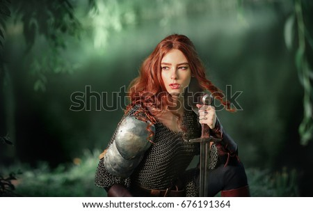 Beautiful red haired girl in metal medieval armor dress with swords sitting in warlike pose near river and looking afar. Fairy tale story about warrior . Glowing light. Warm art work. - Shutterstock ID 676191364