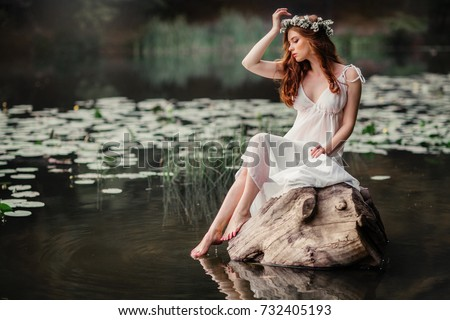 Beautiful red haired girl in white vintage dress and wreath of flowers sitting on a snag in the middle of lake. Fairytale story. Warm art work. - Shutterstock ID 732405193